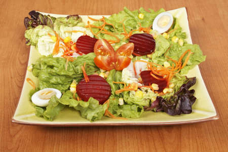 Salad with lettuce, tomatoes, carrot, corn, egg and beet on wooden background. Shallow depth of field Stock Photo - 3366224