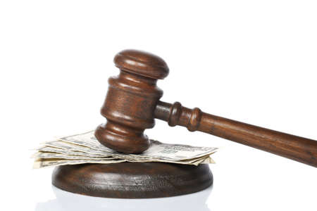 judicial proceeding: Wooden gavel and dollars bills from the court isolated on white background