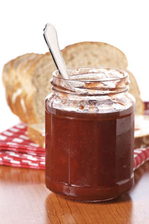 strawberry jam sandwich: Strawberry jam glass jar and bread on square mat. Shallow depth of field