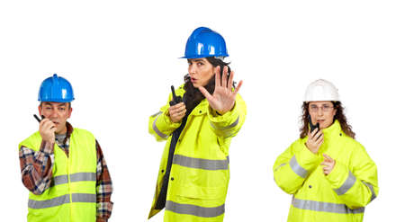 Three construction workers talking with a walkie talkie over a white background. Focus at front photo