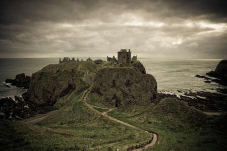 dunnottar castle: A view of Dunnottar Castle under a cloudy sky, Scotland Stock Photo