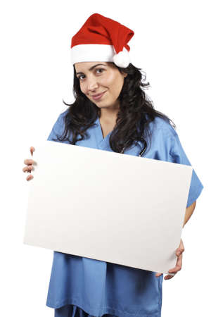 Friendly female doctor in blue scrubs with christmas hat, holding the blank banner on white background  photo