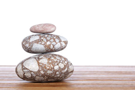 steadiness: Stack of balanced stones with shadow on wooden background