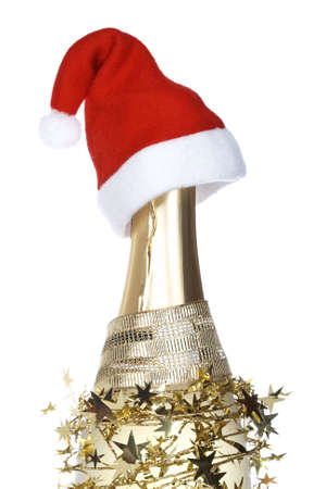 Christmas decoration and champagne bottle with red hat reflected on white background. Shallow depth of field photo