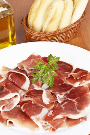 Slices of tasty spanish ham on white dish, oil bottle and bread. Shallow depth of field photo