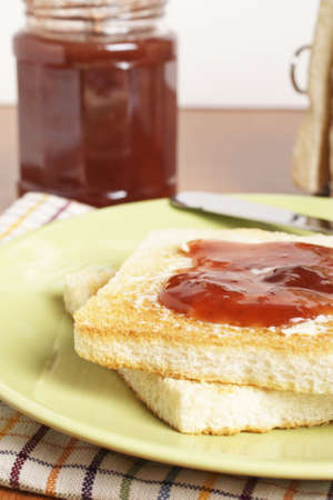 strawberry jam sandwich: Toast with butter and strawberry jam glass jar in the white plate with soft shadow on square mat background. Shallow depth of field