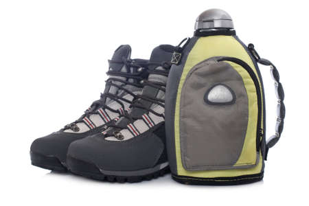 A pair of hiking boots and canteen with shadow, reflected on white background photo