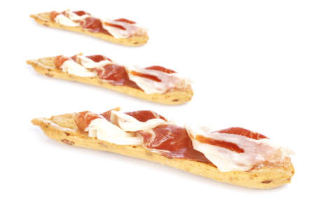 Slices of tasty spanish ham on white background. Focus at front and shallow depth of field photo
