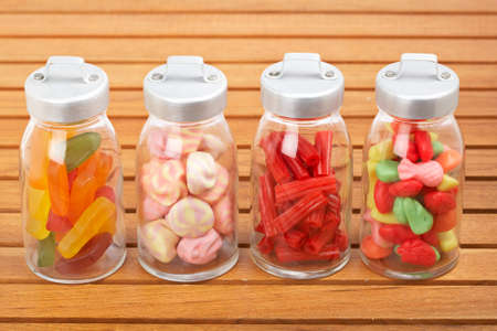 bonbons: Assortment of glass jars with marshmallows, candies and red licorice on wooden background. Shallow depth of field