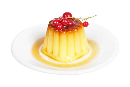 Close-up of a vanilla cream caramel dessert with red currants on white dish. Shallow depth of field