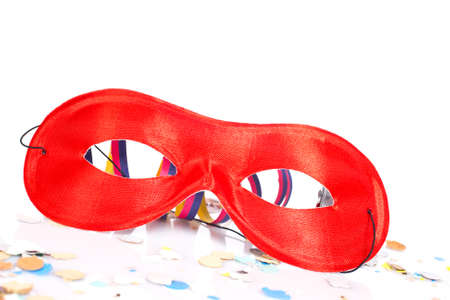 conceal: Red mask and confetti on white background. Shallow depth of field