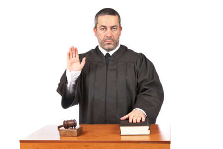 adjourned: A serious male judge taking oath in a courtroom, isolated on white background. Shallow depth of field