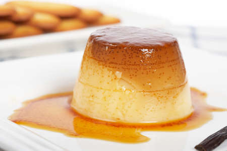 flan: Vanilla cream caramel dessert and cookies on white dish. Shallow depth of field