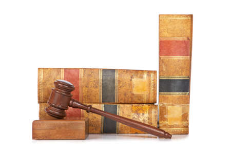 Wooden gavel from the court and old law books reflected on white background. Shallow depth of file