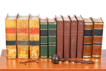 judicial proceeding: Wooden gavel from the court and old law books reflected on white background. Shallow depth of file