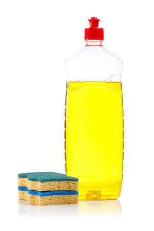 Bottle of yellow dish washing liquid and two sponges reflected on white background photo