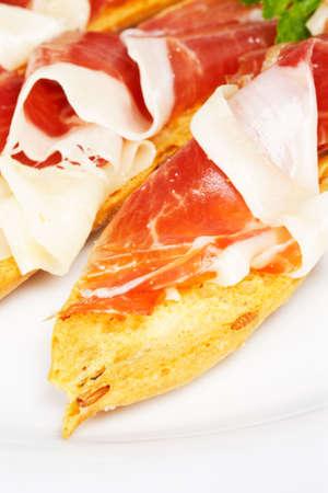 Slices of tasty spanish ham on white dish. Shallow depth of field photo