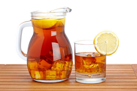 icecubes: Ice tea pitcher and glasss with lemon and icecubes on wooden background. Shallow depth of field Stock Photo