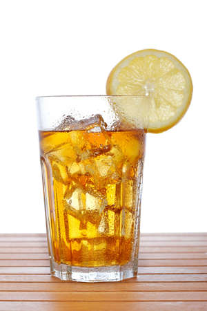 A glass of ice tea with lemon slice on wooden background. Shallow depth of field photo