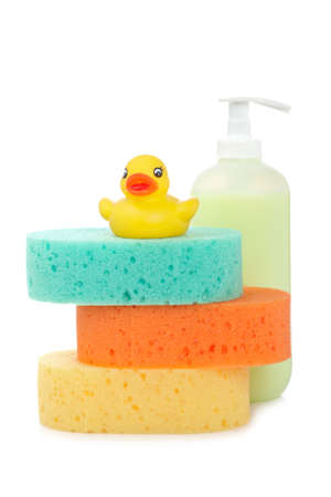 Rubber duck, plastic pump soap bottle and sponges reflected on white background photo