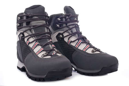 hillwalking: A pair of hiking boots with soft shadow reflected on white background. Shallow depth of field