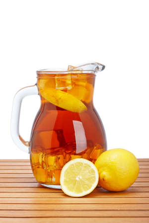 Ice tea pitcher with lemon and icecubes on wooden background photo