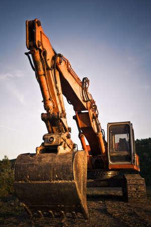 A big orange excavator at construction site Stock Photo