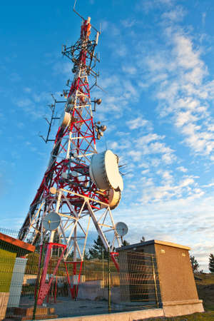 Telecommunications tower with parabolic antennas over a blue sky photo