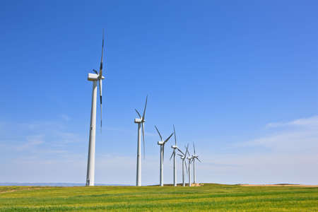 windpower: Wind turbines farm in green field over cloudy sky Stock Photo