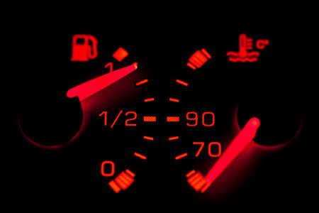 fuel gauge: Car dashboard gauges illuminated over a black background. Shallow depth of field