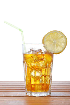 A glass of ice tea with lemon slice and straw on wooden background. Shallow depth of field photo