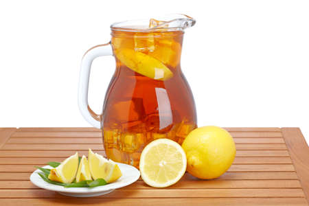 Ice tea pitcher with lemon and icecubes on wooden background