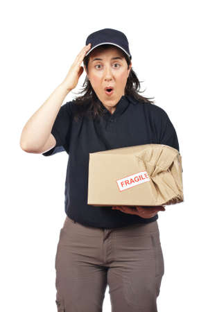 Surprised courier woman holding a damaged package isolated on white background Stock Photo - 5262765