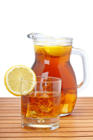 Ice tea pitcher and glasss with lemon and icecubes on wooden background. Focus at front and shallow depth of field photo