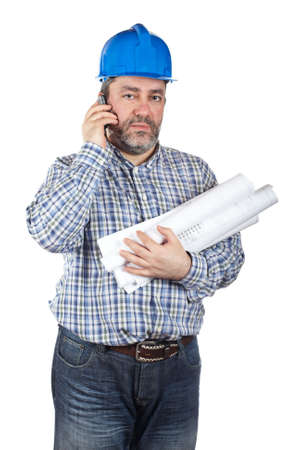 Construction worker holding blueprints and talking with cell phone, isolated on a white background photo