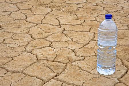 evaporarse: Una botella de agua en seco y fisuras de tierra en el desierto. Profundidad de campo