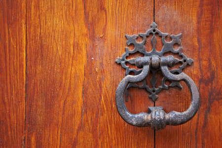 tocar la puerta: Antigua puerta de metal identificador knocker sobre fondo de madera