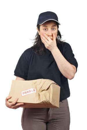 Surprised courier woman holding a damaged package isolated on white background Stock Photo - 6336598