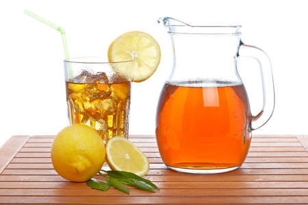 Ice tea pitcher and tumbler with lemon and icecubes on wooden background
