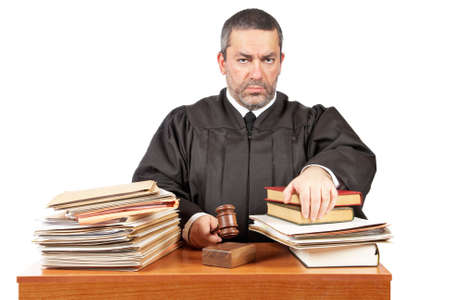 Angry male judge in a courtroom striking the gavel and pronounces sentence photo