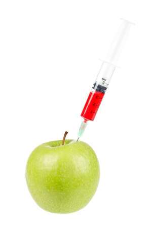 injected: A green apple being injected with a syringe containing red fluid, isolated on white background. Shallow depth of field Stock Photo