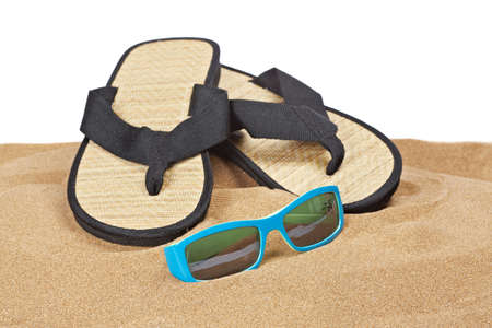 A pair of flipflops or beach sandals and sunglasses with copy space on a white background. Shallow depth of field photo