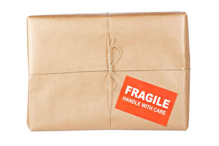 pack string: A fragile parcel wrapped in brown paper and tied with rough twine, isolated on white background. Shallow depth of field Stock Photo