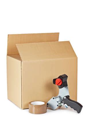 Packaging tape dispenser and shipping box isolated on white background photo