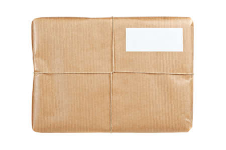 twine: A parcel wrapped in brown paper and tied with rough twine and blank label, isolated on white background. Shallow depth of field