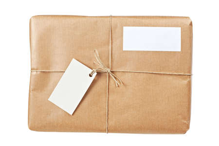 twine: A parcel wrapped in brown paper and tied with rough twine and two blank labels, isolated on white background. Shallow depth of field