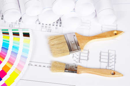 refurbishing: A two paintbrushes and color guide over the house plan. Shallow depth of field