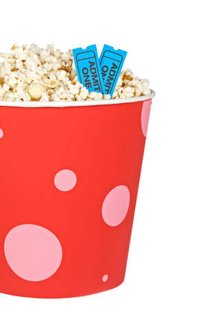 Detail of popcorn in a bucket and two tickets over a white background. Tickets on focus and shallow depth of field photo