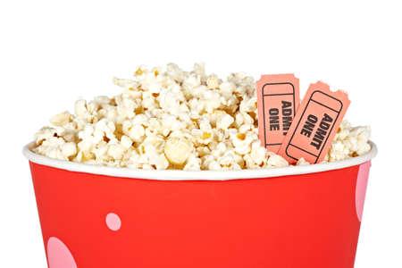 edibles: Dettaglio di popcorn in un secchio e due biglietti su uno sfondo bianco. Biglietti sul fuoco e poca profondit� di campo