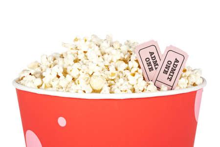 edibles: Dettaglio di popcorn in un secchio e due biglietti su uno sfondo bianco. Biglietti sul fuoco e profondit� di campo